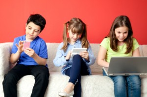 three-kids-children-sitting-on-couch-playing-with-electronics-300x199